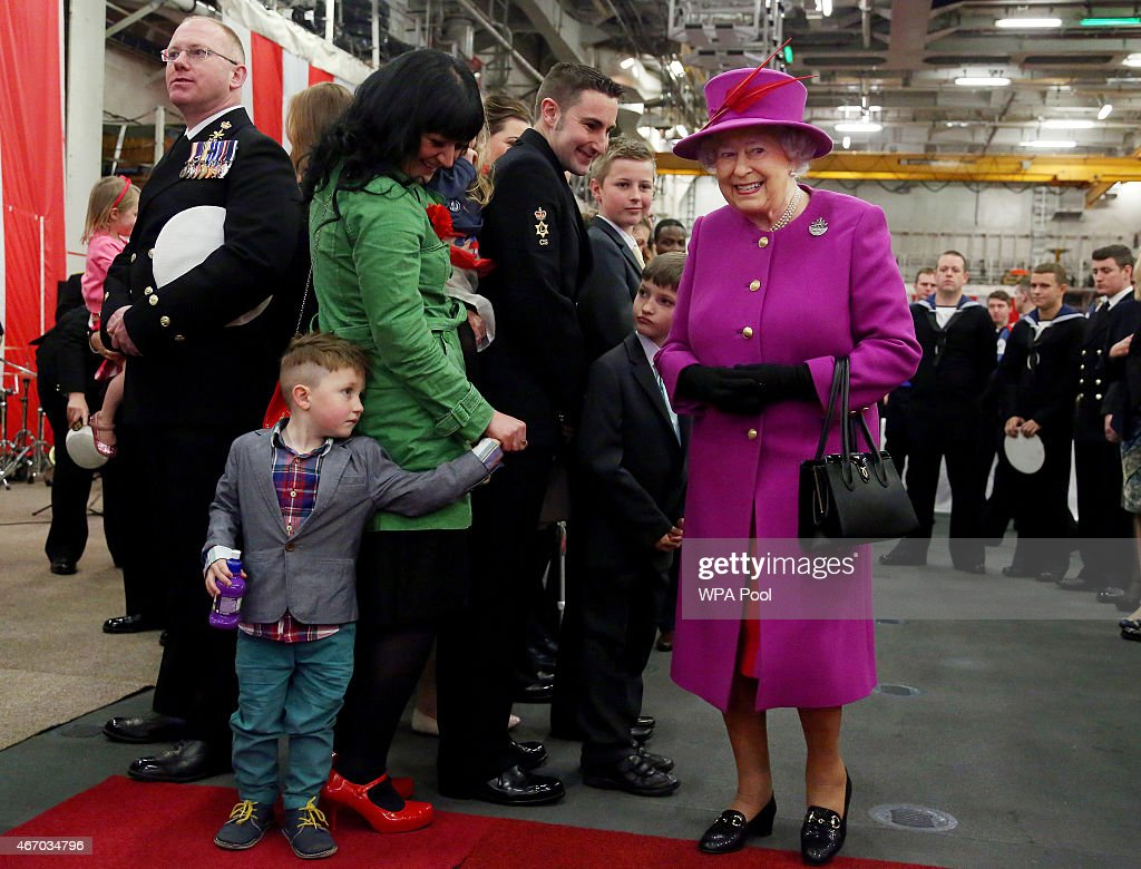 Four-year-old Ashton Akerman (L) reacts while meeting Queen Elizabeth II (R) during a meeting with families and crew on board the Royal Navy's HMS Ocean at Her Majesty's Naval Base Devonport on March 20, 2015 in Plymouth, England.