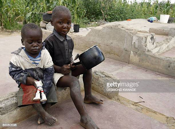 A fouryearold girl scrapes food from a saucepan while her siblings looks on outside of their shack on February 25 2009 in a slum on the outskirts of...
