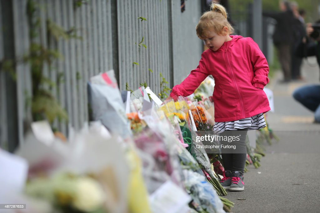 Four-year-old Jasmine Smith views floral tributes as choolchildren arrive at Corpus Christi Catholic College in Neville Road on April 29, 2014 in Leeds, England. A fifteen year old male student has been arrested in connection with the death of teacher Anne Maguire who was fatally stabbed yesterday during lessons at Corpus Christi Catholic Catholic College.