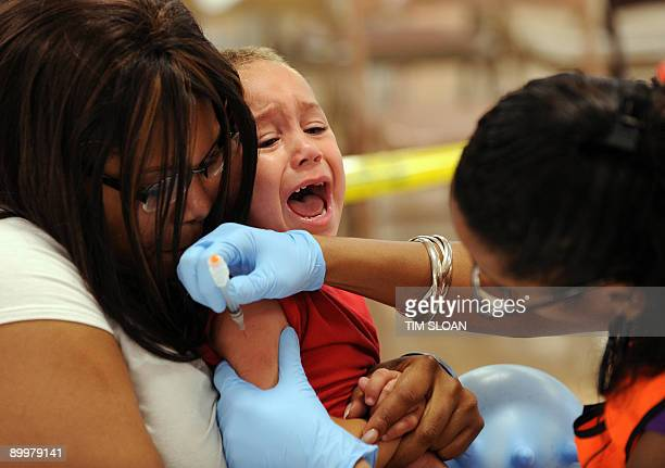 Fouryearold Jovian AshbyThomas is held by his mother Cecila while registered nurse Denise Abreu administers the third of six immunization shots in...