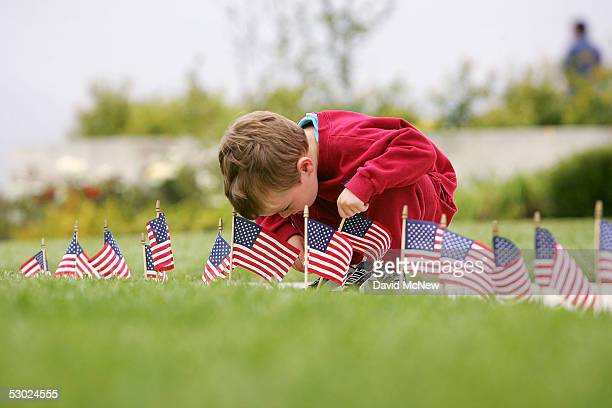 Fouryearold Myles Brasted places a flag in the ground in commemoration of US President Ronald Reagan on the oneyear anniversary of his death at the...