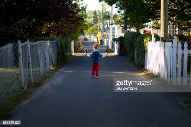 Fouryearold Parker Shores walks down the middle of the street with his action figure toys in Tangier Virginia May 16 where climate change and rising...