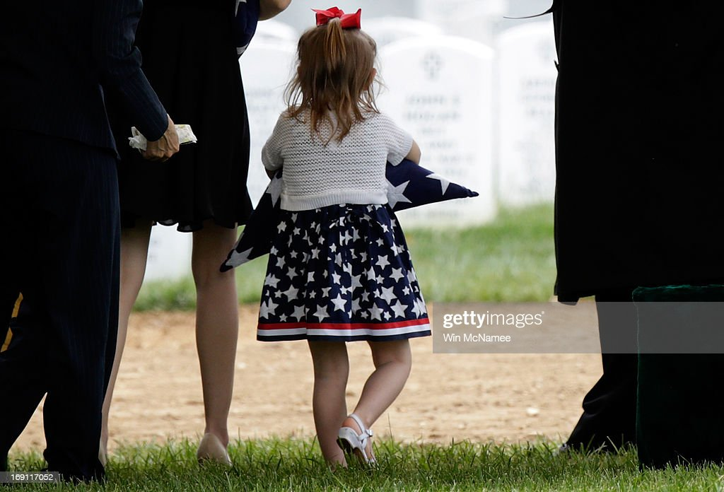 Four-year-old Sophia Phillips carries an American flag presented to her during a burial service for her father, Staff Sergeant Francis G. Phillips, at Arlington National Cemetery May 20, 2013 in Arlington Virginia. Phillips, from Meridian, New York was killed in combat in the Maiwand district of Afghanistan when the vehicle he was riding in was struck by an improvised explosive device.
