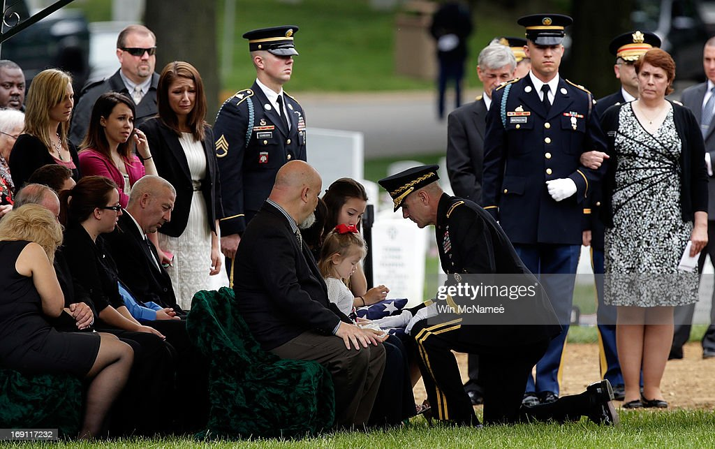 Four-year-old Sophia Phillips is presented an American flag by Brigadier Gen. James Pasquarette during a burial service for her father, Staff Sergeant Francis G. Phillips, at Arlington National Cemetery May 20, 2013 in Arlington Virginia. Phillips, from Meridian, New York was killed in combat in the Maiwand district of Afghanistan when the vehicle he was riding in was struck by an improvised explosive device. Seated next to Sophia Phillips is her mother, Christine Phillips.