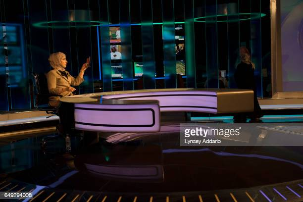 Fouz Awadh al Khamdi a Saudi TV presenter and political news anchor checks her makeup while shooting a live segment at the studio at the Ministry of...