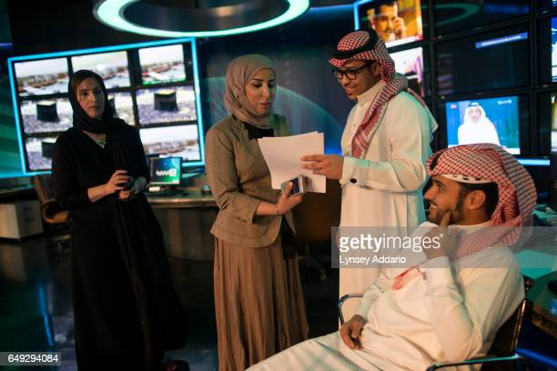 Fouz Awadh al Khamdi a Saudi TV presenter and political news anchor talks with colleagues after shooting a live segment in the studio at the Ministry...