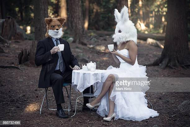 Fox and bunny chatting over afternoon tea, staged.