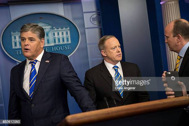 Fox News television personality and political commentator Sean Hannity and White House Press Secretary Sean Spicer stand near the podium after...