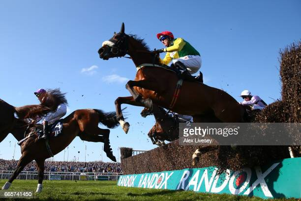 Fox Norton ridden by Robbie Power crashes through a fence on the first time around during the JLT Melling Chase on Ladies Day at Aintree Racecourse...