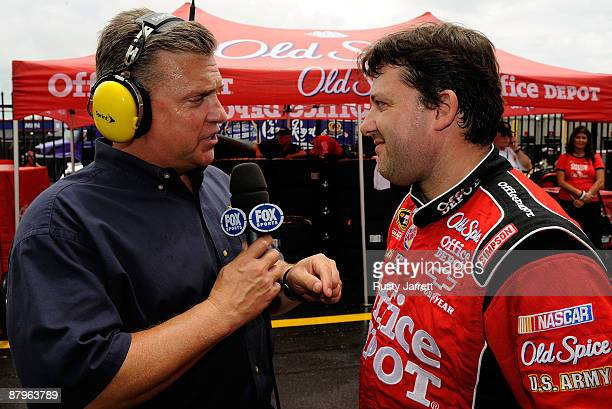Fox personality Steve Byrnes speaks with Tony Stewart driver of the Office Depot/Old Spice Chevrolet during a red flag due to rain for the NASCAR...