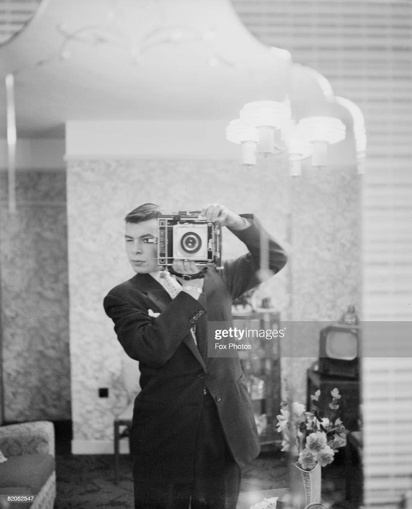 A Fox Photos staff photographer captures his own image in a mirror, circa 1948.