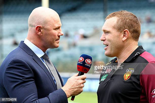 Fox television commentator Barry Hall talks with Lions head coach Justin Leppitsch before the AFL round one match between the West Coast Eagles and...