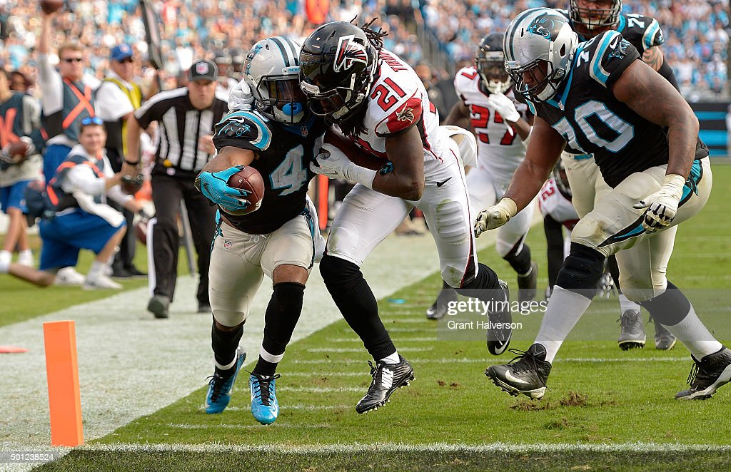 Fozzy Whittaker #43 of the Carolina Panthers extends the ball across the goal line against Desmond Trufant #21 of the Atlanta Falcons in the 3rd quarter during their game at Bank of America Stadium on December 13, 2015 in Charlotte, North Carolina.
