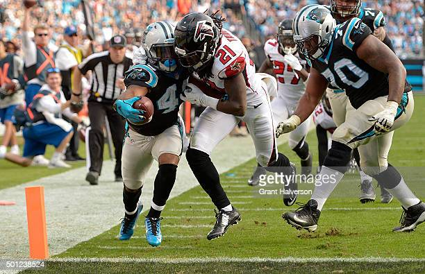 Fozzy Whittaker of the Carolina Panthers extends the ball across the goal line against Desmond Trufant of the Atlanta Falcons in the 3rd quarter...