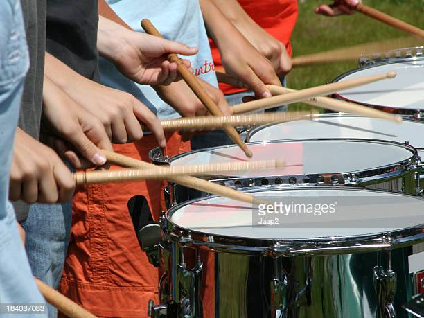 Fragment of kids drumming outdoor with shallow DOF