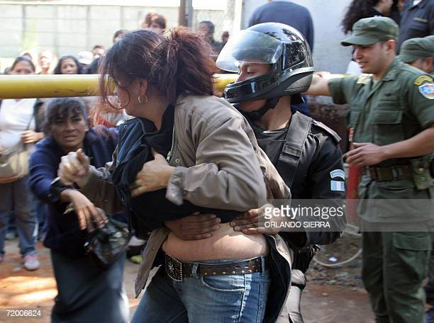 Agentes de la Policia Nacional Civil detienen a familiares de convictos que se enfrentan a golpes en las inmediaciones de la Granja Modelo de...
