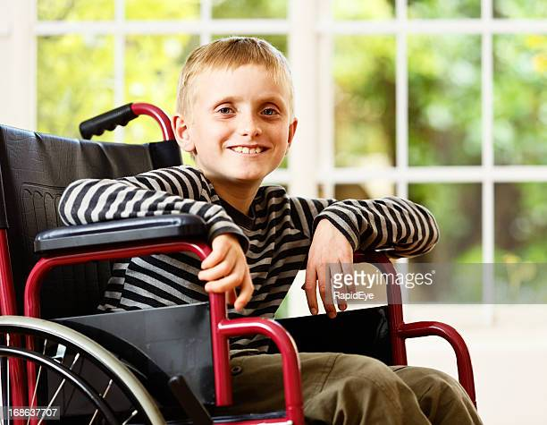 Frail little boy in wheelchair smiles bravely and optimistically