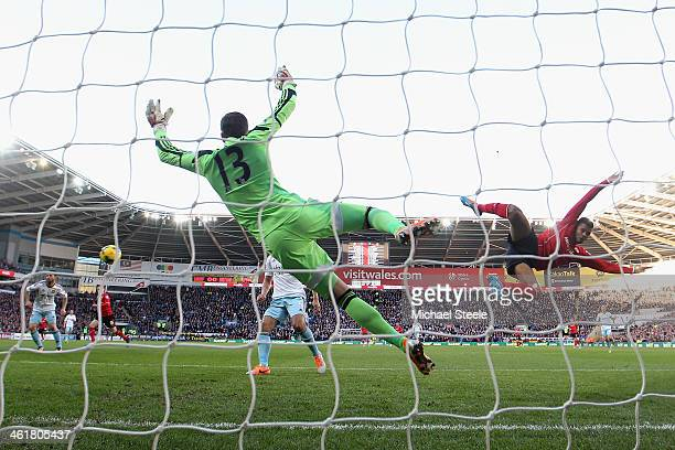 Fraizer Campbell of Cardiff City is airbourne as he attempts to connect with the ball as goalkeeper Adrian of West Ham United spreads himself duering...