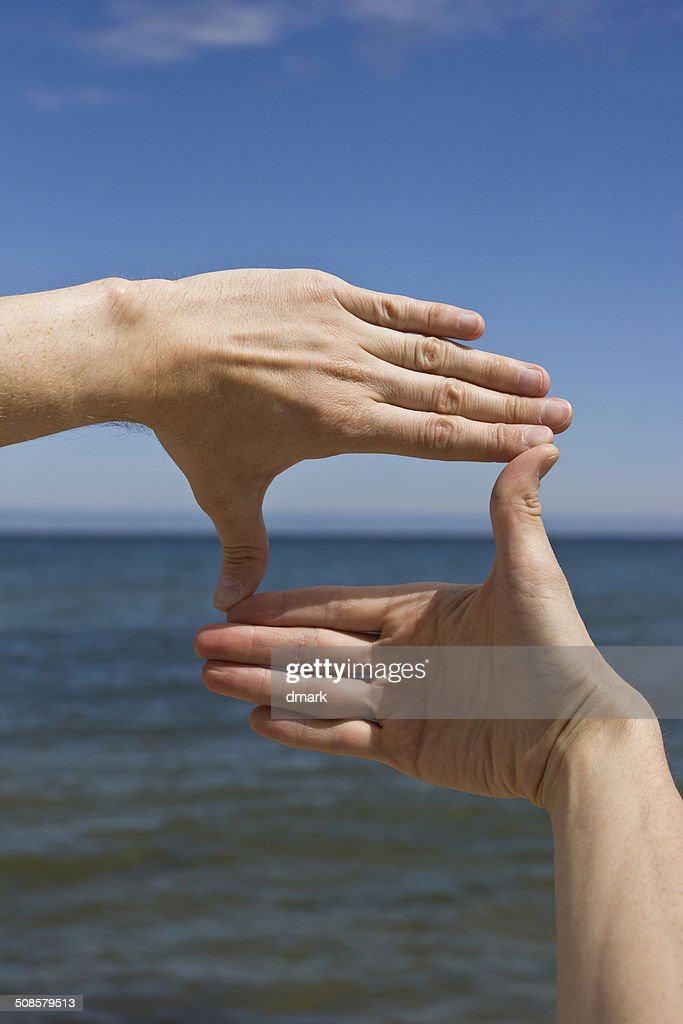 Frame made of hands against the sea : Stockfoto