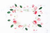 Frame made of rose flowers on white background. Flat lay, top view