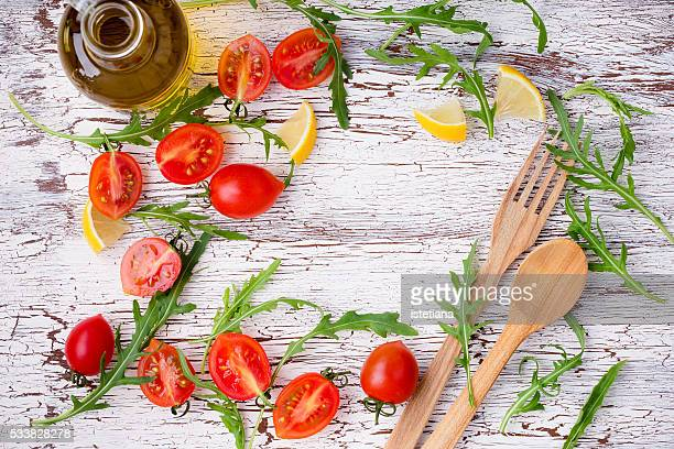 Frame of fresh raw salad ingredients and wooden spoon and fork on rustic wooden   table with central copy space, overhead view