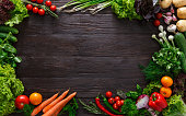 Frame of fresh organic vegetables on wood background. Healthy natural food on rustic wooden table with copy space. Tomato, lettuce, carrot, garlic, pepper and other cooking ingredients top view