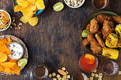 Frame of fried chicken, beer, sauces, potato chips, nachos, peanuts, pistachios and crackers on wooden table, top view