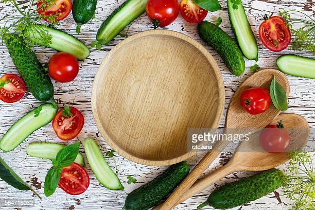 Frame of vegetables for summer salad with wooden bowl in  center of composition viewed from above, healthy eating and diet food concept