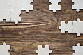 Incomplete wooden puzzles on brown wooden desk, top view, flat lay. Frame with puzzle. The concept of logical thinking, business, conundrum. Business concept with  jigsaw puzzle on wooden background.