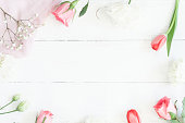Frame with rose flowers and tulip om wooden white background. Flat lay, top view