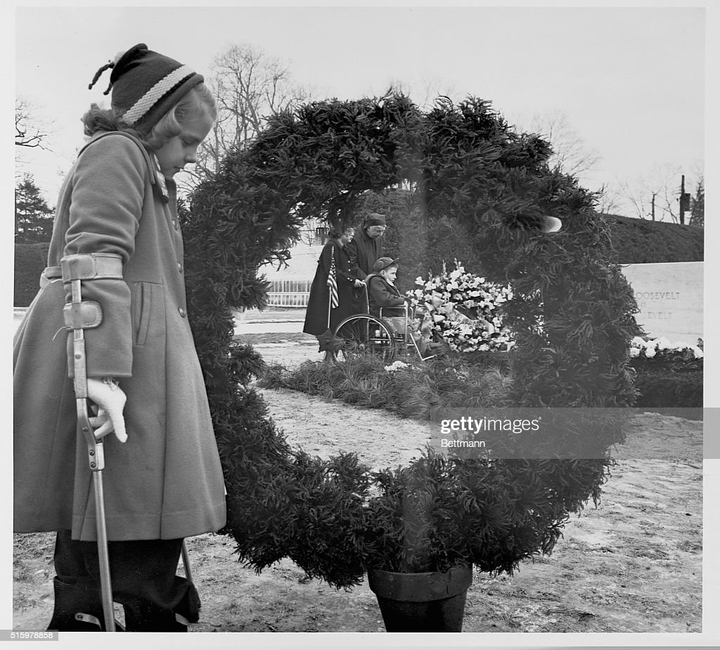 Framed by a large wreath Eleanor Roosevelt joins March of Dimes children in wreathplacing ceremonies at the grave of the late President Franklin...