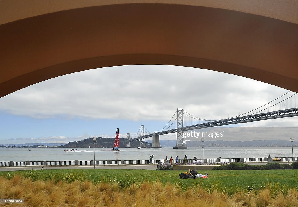 Framed by the sculpture Cupid's Span, Emirates Team New Zealand is towed near the Bay Bridge before the start of the Louis Vuitton Cup in San Francisco, California on August 25, 2013. AFP PHOTO / Josh Edelson