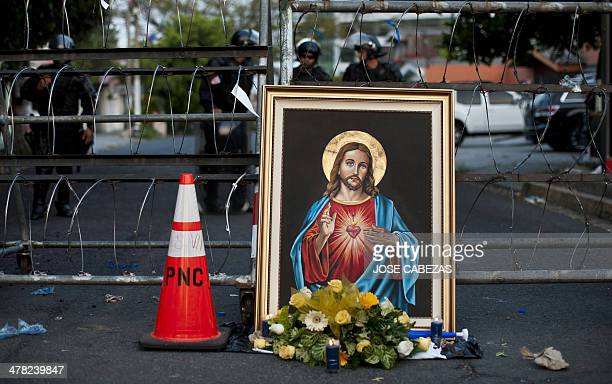 A framed image of the Sacred heart of Jesus Christ remains outside the electoral authority headquarters in San Salvador on March 12 as supporters of...