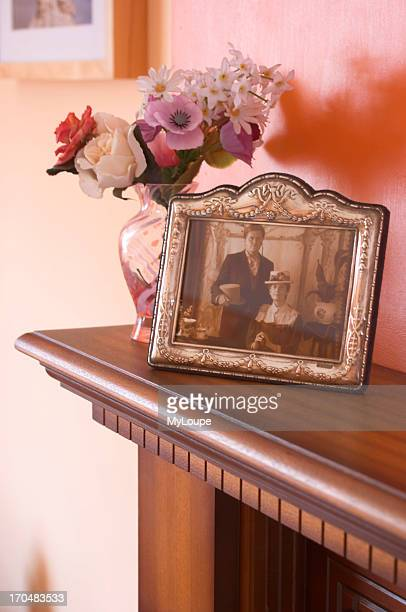Framed photograph and vase of flowers on typical British mantelpiece