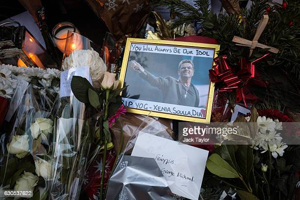 A framed photograph of George Michael is left among tributes of flowers candles and messages left at the home of the pop music icon in The Grove...