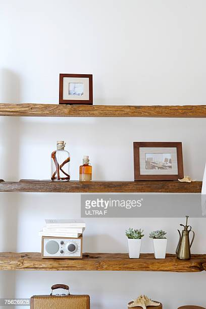 Framed photographs, decorative jars and potted plants on natural wooden shelves