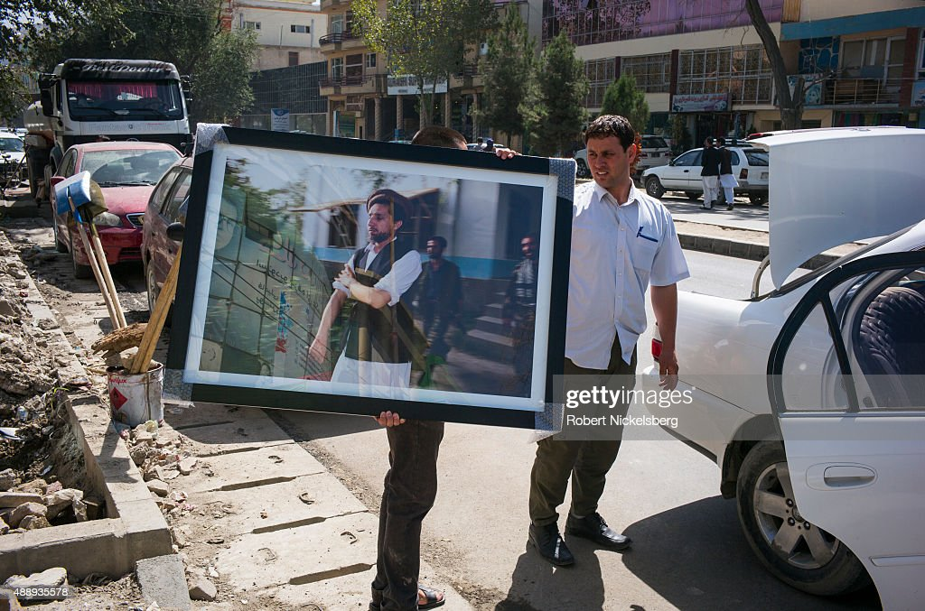 A framed picture of former mujahideen leader <a gi-track='captionPersonalityLinkClicked' href=/galleries/search?phrase=Ahmad+Shah+Massoud&family=editorial&specificpeople=239231 ng-click='$event.stopPropagation()'>Ahmad Shah Massoud</a> is carried to a car August 30, 2015 in Kabul, Afghanistan. A political and military leader, Masood was assassinated on September 9, 2001 by two Arab men from Al Qaeda disguised as journalists, two days before the September 11, 2001 attack on New York City and Washington, DC.