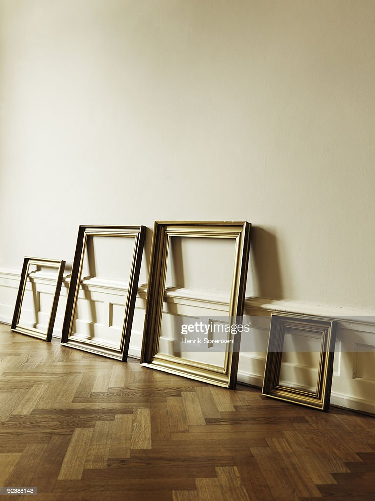 Frames leaning against empty interior wall : Stock Photo