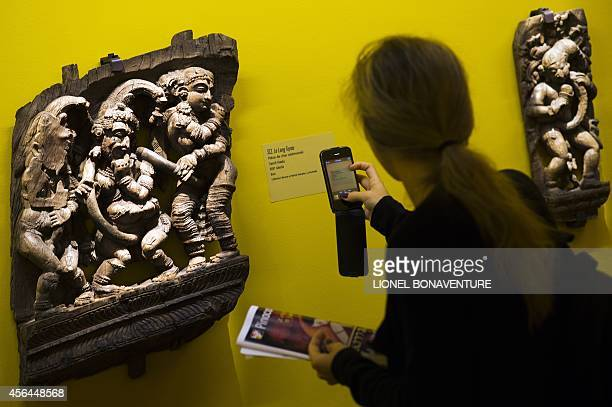 Fran Blandy A woman takes picture of a sculpture as she visits the exhibition The KamaSutra spirituality and erotism in Indian art at the Paris'...