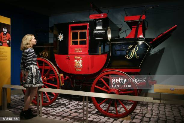01 GMT / Fran LangdonDevlin a staff member poses next to a Mail Coach circa 1800 during a media preview of the new Postal Museum and the Mail Rail...