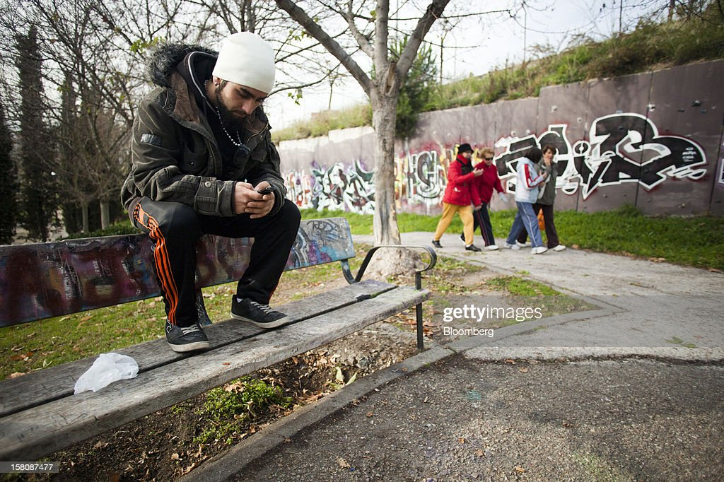 Fran Lopez, a jobless electrician, checks his mobile phone on a street bench near his home in Madrid, Spain, on Monday, Dec. 10, 2012. The jobless rate in Lopez's native Spain stands at 26 percent, jostling with Greece for the rank of highest on the continent. Photographer: Photographer: Angel Navarrete/Bloomberg via Getty Images