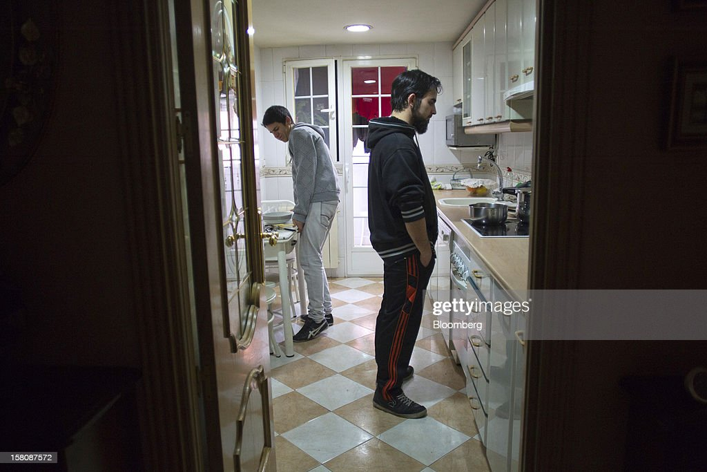 Fran Lopez, a jobless electrician, right, cooks with his brother Carlos, in the kitchen of his parent's home in Madrid, Spain, on Monday, Dec. 10, 2012. The jobless rate in Lopez's native Spain stands at 26 percent, jostling with Greece for the rank of highest on the continent. Photographer: Photographer: Angel Navarrete/Bloomberg via Getty Images