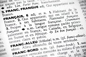 Macro shot with focus on the word français and its definition in a french dictionary.