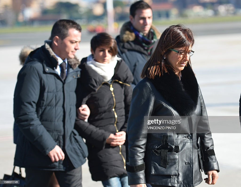 Franca (R), sister of Italian marine Massimiliano Latorre, arrives with other relatives at Ciampino's airport, near Rome, on December 22, 2012. An Indian court allowed two Italian marines awaiting trial for shooting two fishermen to go home for Christmas, despite prosecution fears that they will not return. The marines shot dead the fishermen off India's southwestern coast near the port city of Kochi in February while guarding an Italian oil tanker, but they deny murder on the grounds that they mistook their victims for pirates.