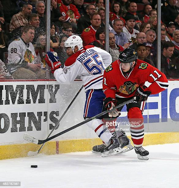 Francais Bouillon of the Montreal Canadiens hits the boards as he chases the puck with Jeremy Morin of the Chicago Blackhawks at the United Center on...