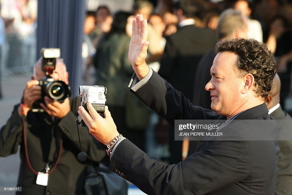 American actor Tom Hanks (R) films the crowd as he arrives for the preview of his latest film 'The Terminal' at the 30th Deauville American film festival in Deauville, 04 September 2004. Steven Spielberg, the director of 'The Terminal' is being honoured at this year's festival for his contribution to American film. AFP PHOTO/JEAN PIERRE MULLER