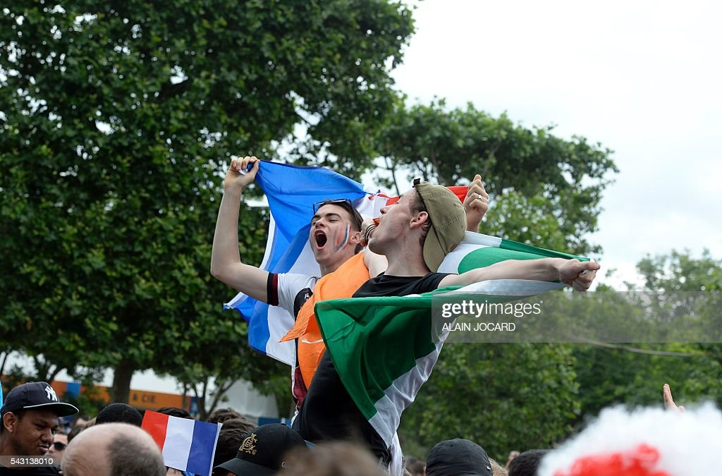 France and Ireland supporters cheer and shout as they watch the Euro 2016 tournament round of 16 football match between France and Republic of Ireland on June 26, 2016 at the Champ-de-Mars fanzone in Paris. / AFP / ALAIN