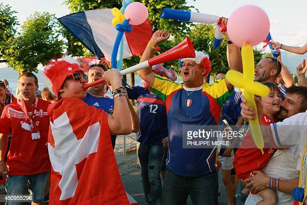 France and Switzerland's fans cheer before the start of the FIFA 2014 World Cup football match France vs Switzerland on June 20 as locals watch the...