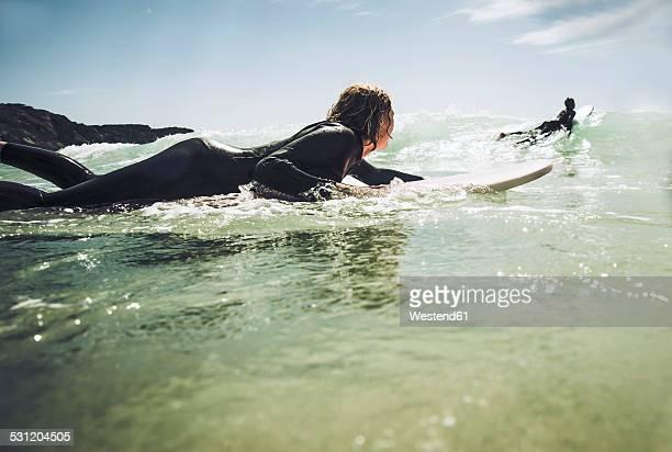 France, Bretagne, Camaret sur Mer, Teenagers surfing at Atlantic coast
