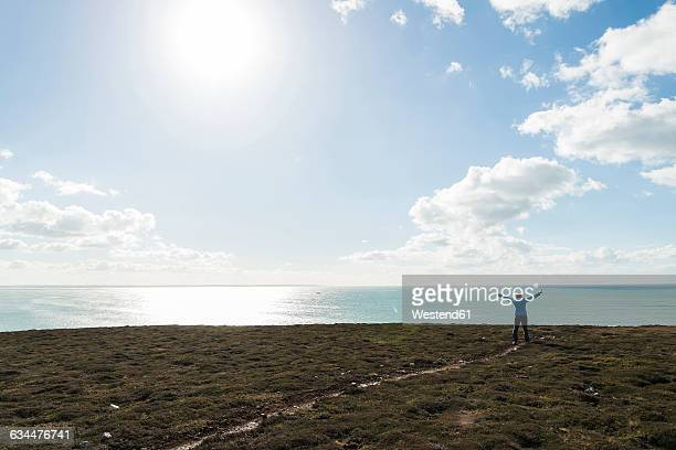 France, Bretagne, Finistere, Crozon peninsula, woman standing at the coast with outstretched arms